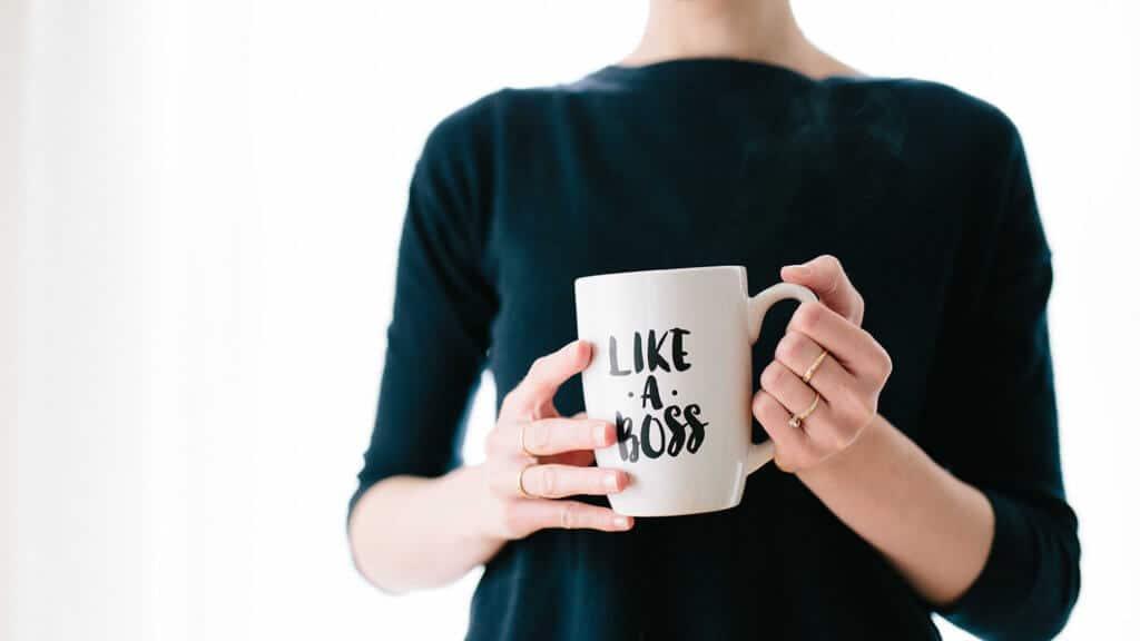 """Frau in schwarz gekleidet hält eine Kaffeetasse in der Hand mit der Aufschrift """"Like a boss""""."""