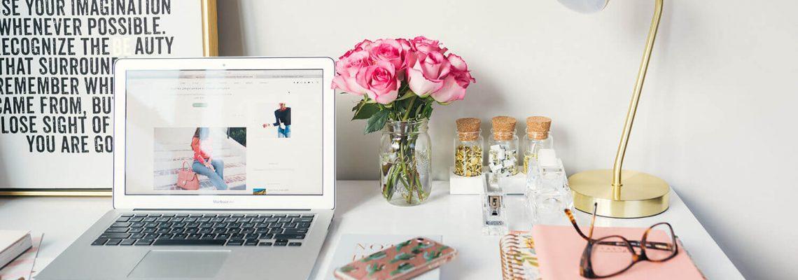 Laptop auf einem Tisch, im Hintergrund ein Bild mit einem inspirierenden Zitat, Blumen